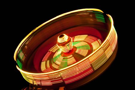 A spinning fair ride at night leaving a trail of circular lights on a black background. Archivio Fotografico