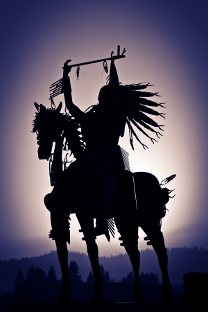 A silhouette of a Native American on a horse made from metal with distant mountains and a purple haze vignetting. photo