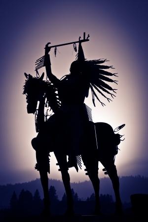 indio americano: Una silueta de un nativo americano en un caballo hecho de metal de montañas distantes y un viñeteado neblina púrpura.