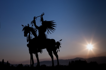 A silhouette of a Native American on a horse made from metal with eight rays emanating out from the setting sun in the distance above hazy mountains. Imagens