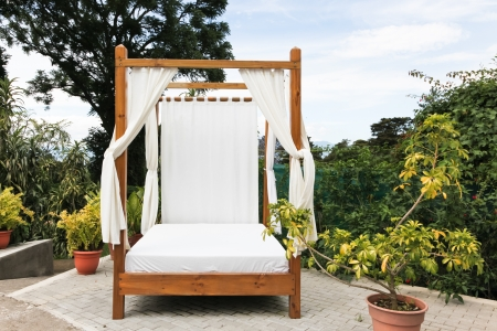 bed sheet: A wooden outdoor bed with white linens and privacy curtains on a brick patio at a tropical resort.