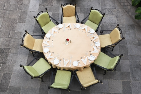 Looking down at a large round table set for nine people on a brick patio. photo