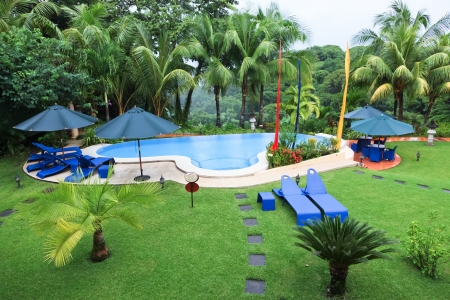 A swimming pool and patio furniture in the rain surrounded by lush green tropical forest and grass.