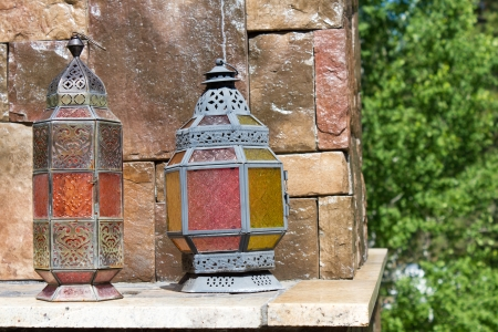 Antique looking metal lanterns with colorful stained glass panels sitting on a rock shelf of a outdoor rock fire place. photo