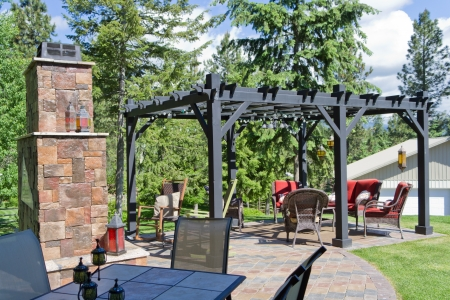 outdoor fireplace: A backyard patio area with a dining table in the shade, a rock fireplace, and a sitting area under a wooden trellis. Stock Photo