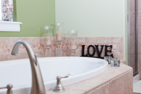A white bathtub by a window decorated with sea shells and candles next to a wooden sign cut out to say love. Stock Photo