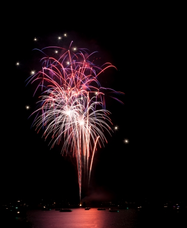 Pink, purple, white, and red fireworks with white sparkles cascade down on boats on Lake Coeur d Alene, Idaho  Archivio Fotografico
