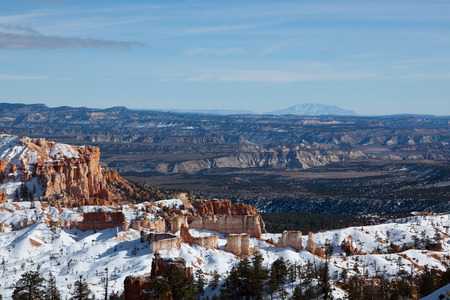 Bryce Canyon National Park in Utah on a sunny winter day showing colorful canyon formations lightly covered in snow. photo