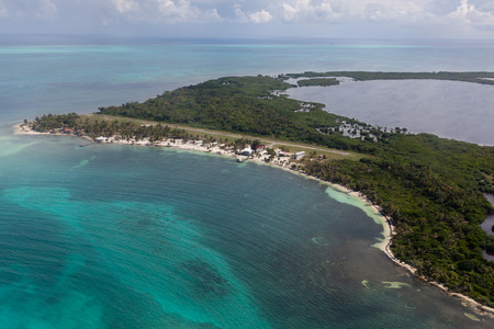 An aerial view of the northern beach of Lighthouse Reef and airstrip off the coast of Belize in the Caribbean Ocean.