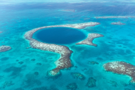 An aerial view of the coral reef and deep cave that make up the famous diving spot of the Blue Hole in the Caribbean Ocean off the coast of Belize. Imagens - 24568630