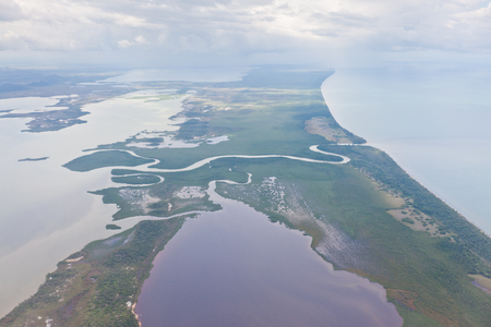 tourism in belize: A river outlet curving through tropical jungle from an inland body of water to the Caribbean ocean on the coast of Belize   Recent heavy rains and flooding