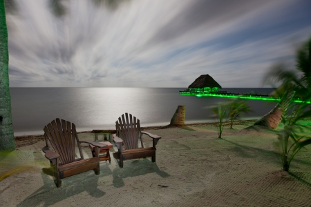 A night time beach with moonlight and green accent lights highlighting a covered dock and beach chairs in a long exposure