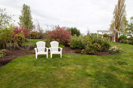 Two white lawn chairs sit next to each other in a landscaped yard with manicured grass  photo