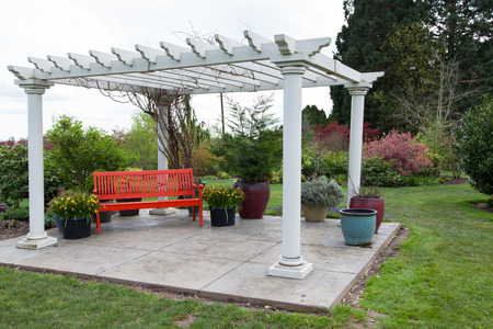 A large white wooden gazebo structure on a concrete platform and a red bench underneath in a landscaped yard.