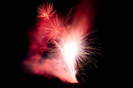 A man stands under a large display of vibrant fireworks as they are set off.