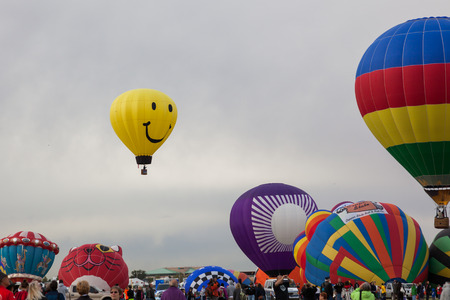 smiley face car: Albuquerque, NM, October 8:  A smiley face balloon floats above others not yet launched at the Balloon Fiesta in Albuquerque, New Mexico on October 8th, 2014.