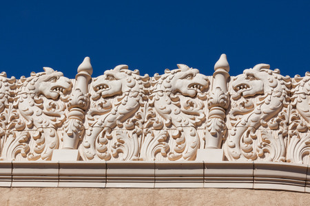 A southwestern building with tiles creating a dragon theme are used as decoration along the top edge.