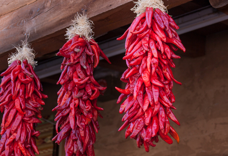 Groups of red chile peppers hanging in a southwestern open air market to dry out. Archivio Fotografico