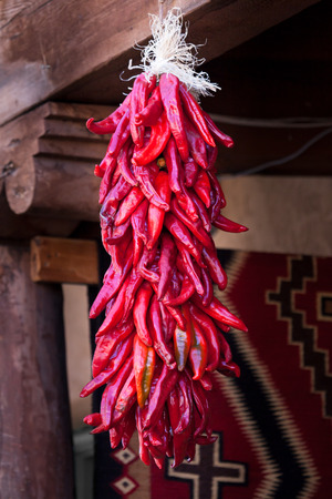 A group of red chile peppers hanging in a southwestern open air market to dry out.