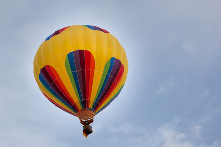 A colorful round hot air balloon lifting up into a light blue sky with wispy clouds.