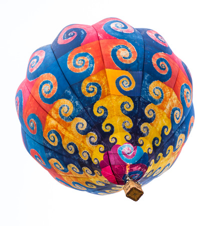 A colorful patterned hot air balloon floating overhead isolated on a white background.