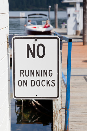 stating: A sign posted stating no running on docks with a background of boats and a lake.