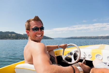 lake shore drive: A smiling handsome young man behind the wheel of a yellow speedboat on Lake Coeur dAlene, ID.