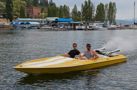 yellow boats: Two men in a yellow speedboat going slow through a marina with boats and buildings in the background.