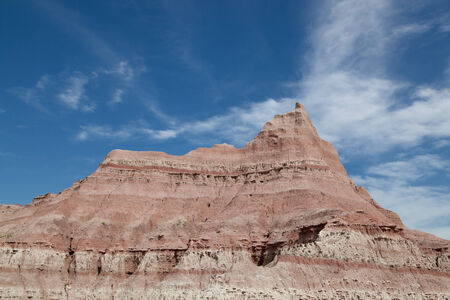 rock layers: Layers of clay and rock carved out by erosion creating a dramatic peak against a blue sky with white wispy clouds in Badlands National Park, South Dakota. Stock Photo