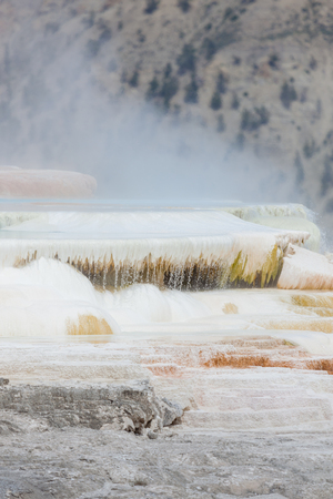 Colorful Mammoth Hot Springs cascading down a mountain side with steam rising and mountain landscape background at Yellowstone National Park. Stock Photo