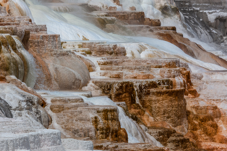 Steaming hot water flowing over colorful mineral and bacteria formations at Yellowstone National Park. Stock Photo