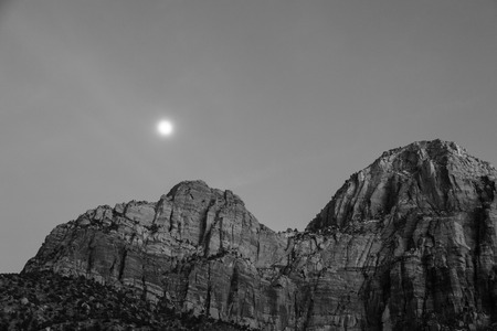 ut: A black and white image at twilight with a bright rising moon creating a soft glow above the mountains in Zion National Park, UT.