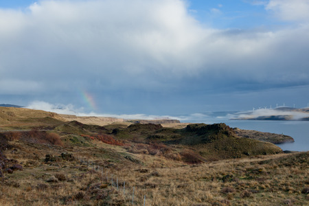 washington landscape: The landscape of the Columbia River Gorge from the Washington side looking over dry rocky land with a rainbow under stormy skies and over low fog.