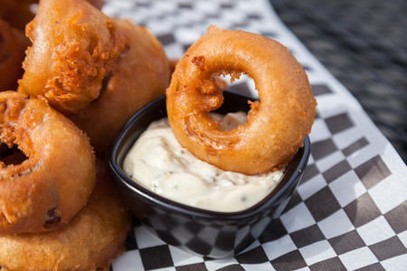A fat beer battered onion ring resting on white tartar dipping sauce at a patio table.