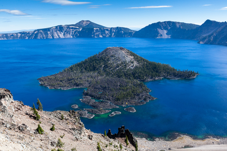 The volcanic cone of Wizard Island with trees growing in the rock and lava flow located in the blue waters of Crater Lake, Oregon.