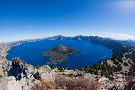 A wide angle view of Crater Lake which is the deepest and bluest lake in the United States with Wizard Island in the middle and a rim of high volcanic rock. Stock Photo