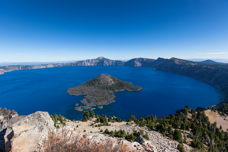 Looking a mile down from the rim to the surface of Wizard Island in Crater Lake to volcanic rocks with trees surrounded by deep blue water.