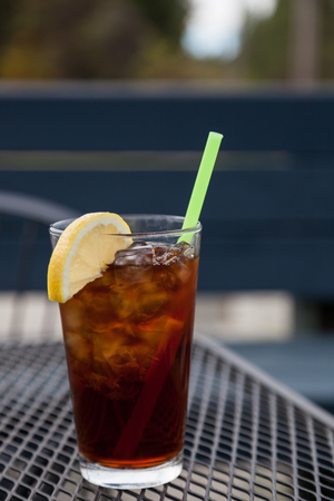 A glass of refreshing iced tea with a lemon and green straw sitting on a patio table.