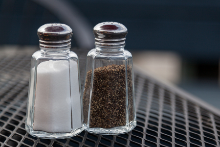 Glass salt and pepper shakers on an outdoor table top at a restaurant.