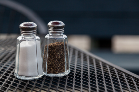 Glass holders full of salt and pepper sit on a patio table of a restaurant. Stok Fotoğraf - 82891346
