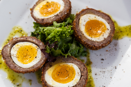 Four soft yolked eggs surrounded by breaded and fried sausage presented on a white plate with garnish and drizzle.