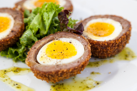 A soft yolk egg in a shell of deep fried sausage with spices and garnish. Imagens