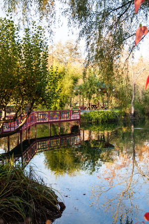 A calm pond reflecting a red bridge and a gazebo in a park like setting during fall in California.