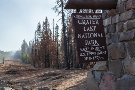 CRATER LAKE, OREGON - October 9 2015: A National Park Service sign marking the boundary of Crater Lake National Park is next to a burnt section of trees damaged by the 2015 National Creek Complex fire in Crater Lake, Oregon.