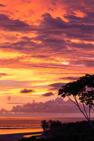 Vivid colors in the clouds and sky as the sun sets behind the horizon leaving a beautiful display of natural beauty seen form the top of a mountain in Uvita, Costa Rica