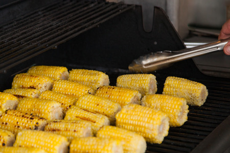 Small sections of yellow corn on the cob lined up on a gas barbecue and being turned by kitchen tongs.