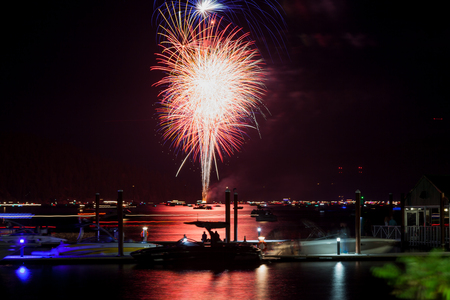 Beautiful Fourth of July fireworks glowing over Lake Coeur d'Alene in Idaho with several boats crowding the water and the dock. Stock Photo