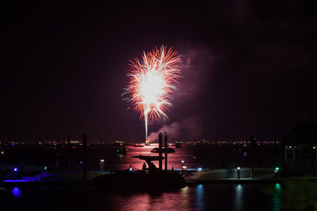Beautiful Fourth of July fireworks glowing over Lake Coeur d'Alene in Idaho with several boats crowding the water and the dock. 写真素材
