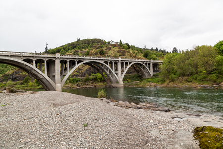A concrete arch bridge spanning over the green waters on the South Umpqua River in Oregon.