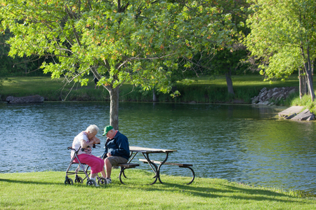 SYCAMORE, ILLINOIS - May 23, 2014: An elderly couple sitting at a picnic bench by a pond in the afternoon at Sycamore RV Park  in Sycamore, IL on May 23, 2014.